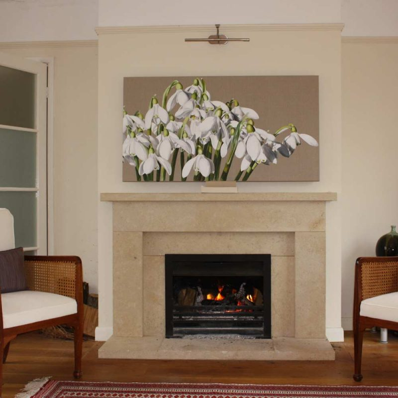 White snowdrops galanthus acrylic on linen painting by UK floral artist Sarah Caswell hung above a fireplace in a living room