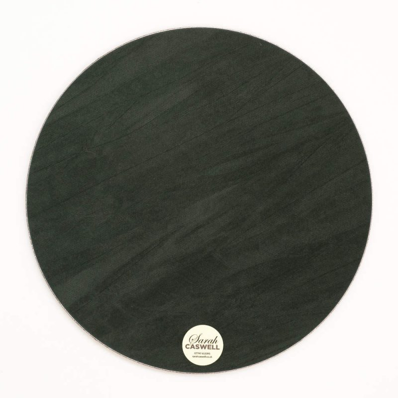 Green baize backing of round melamine tablemat