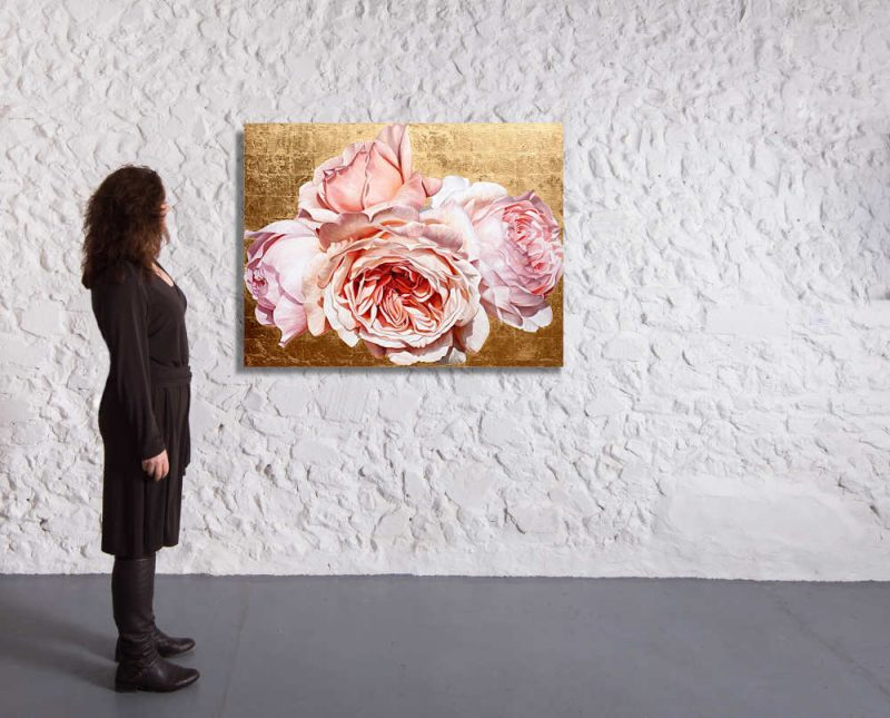 Original acrylic painting by Sarah Caswell of Coral pink David Austin 'Jubilee Celebration' roses in bright sunshine on red gold. Shown in a gallery setting.